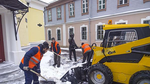 Уборка снега в старой части города у фигурки аптекаря